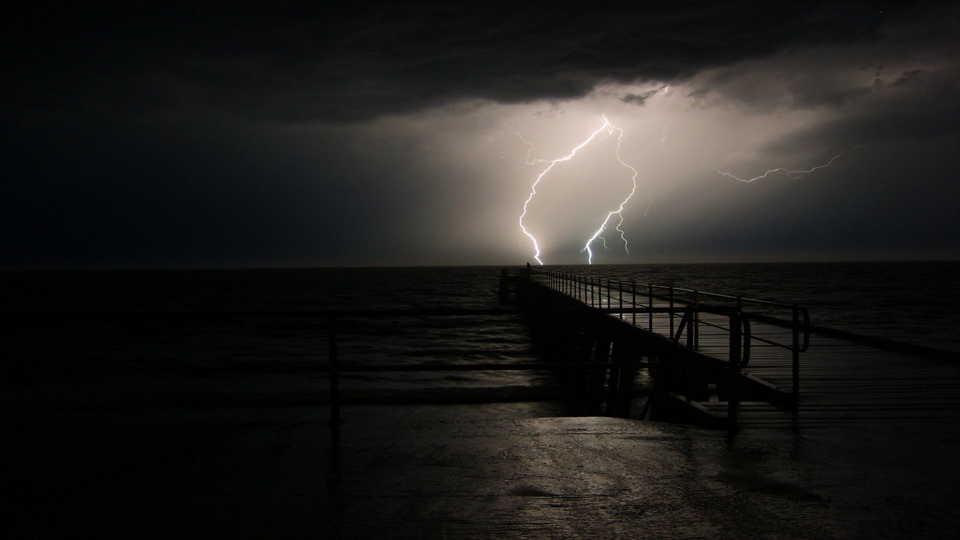 A storm approaching a pier with lightning in the distance.